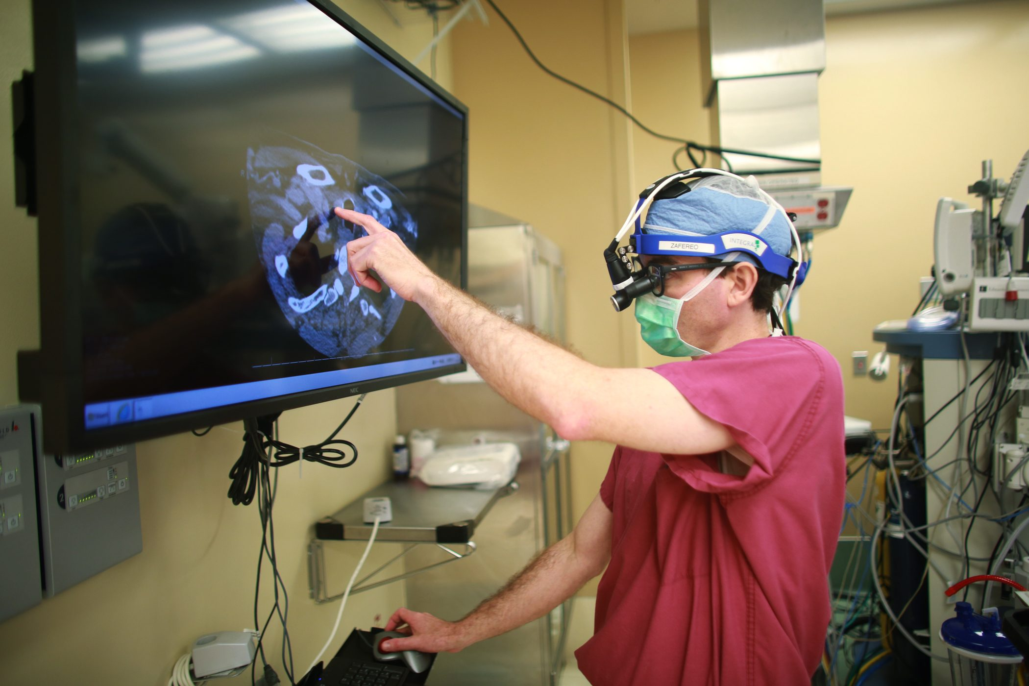 Mark Zafereo, M.D., looking at a computer monitor during surgery