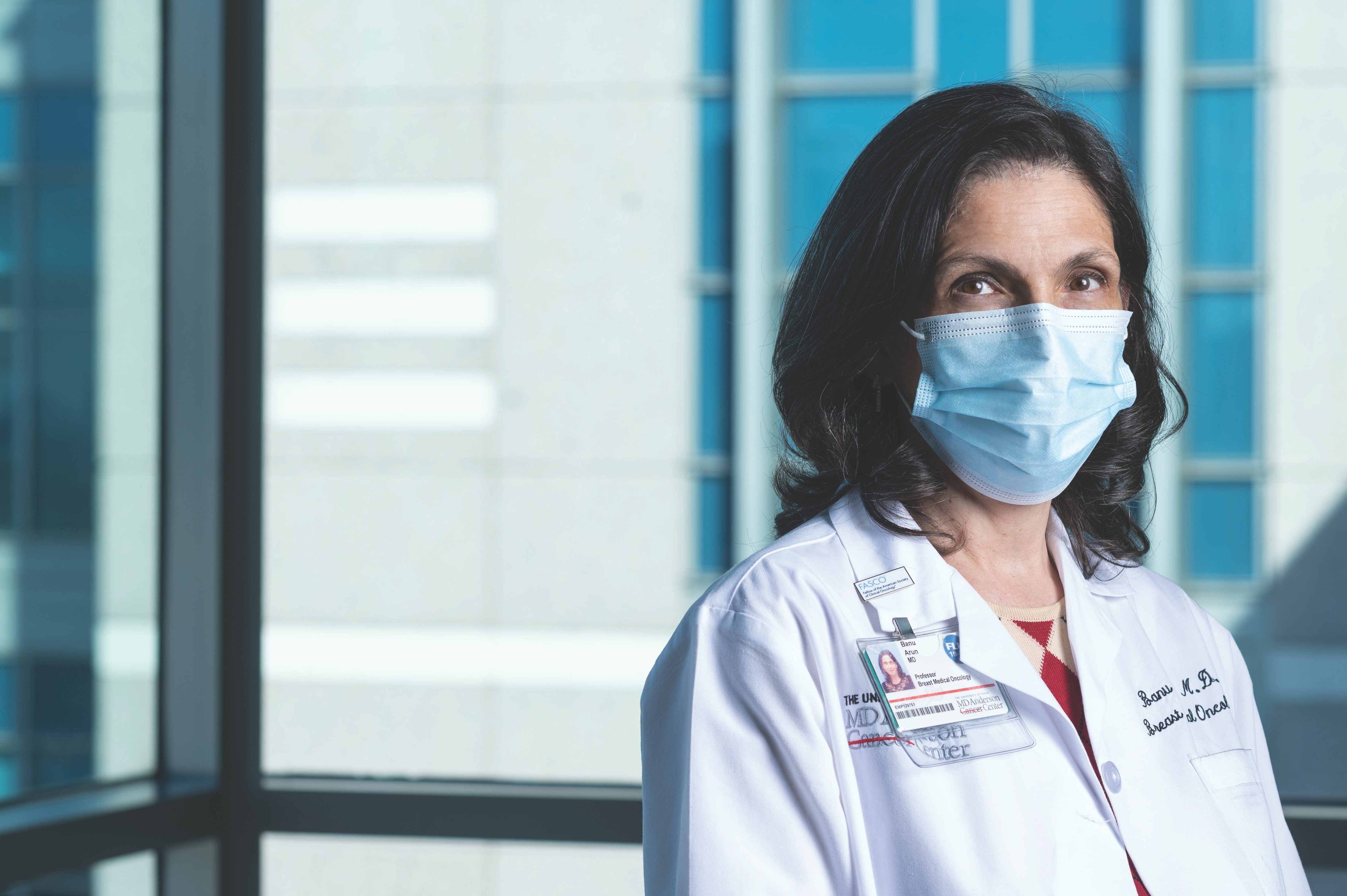 Genetic counseling and testing specialist Banu Arun, M.D., stands wearing a medical-grade face mask