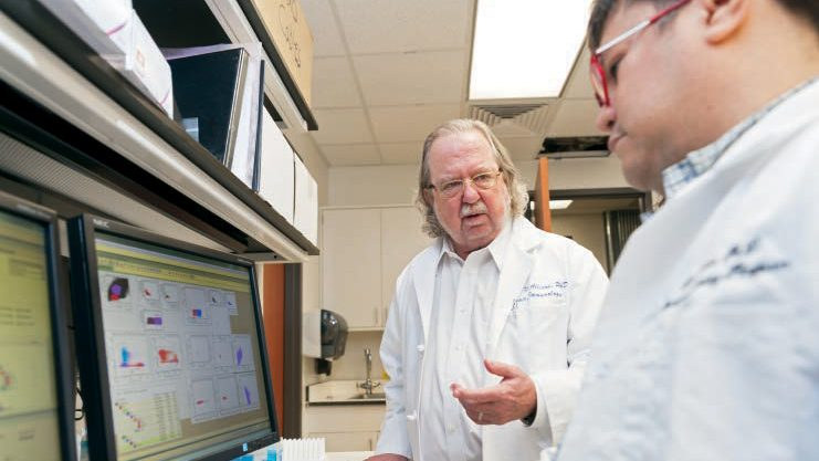 James P. Allison, Ph.D., in a laboratory with a researcher