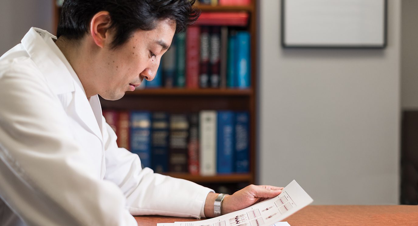 Koichi Takahashi, M.D., reading a medical report