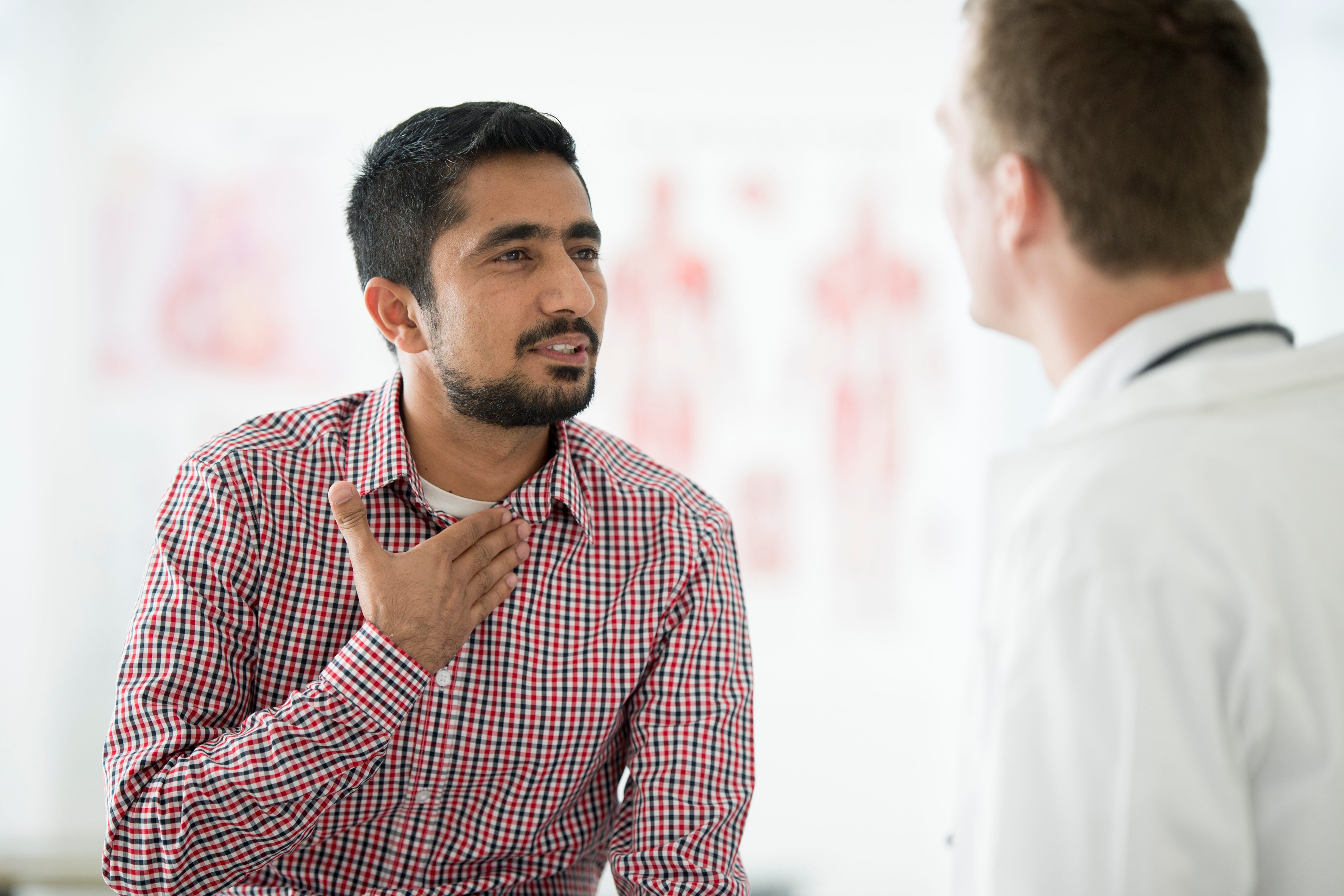 Male patient pointing toward neck while speaking to physician